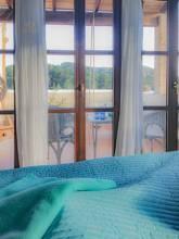 Schlafzimmer im OG mit Blick auf Balkon und die umliegende Landschaft